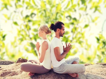 fitness, sport, meditatie en lifestyle concept - lachende paar maken van yoga oefeningen in openlucht Stockfoto