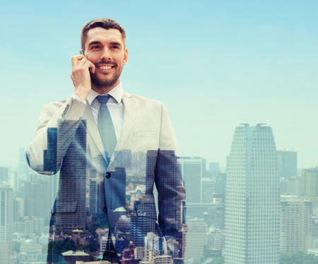 talk: business, technology, communication and people concept - smiling businessman with smartphone talking over city background