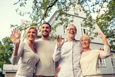 familias felices: familia, generación, el hogar, el gesto y concepto de la gente - familia feliz de pie delante de la casa agitando las manos al aire libre