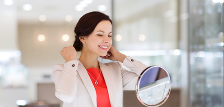 gold silver: sale, consumerism, shopping and people concept - happy woman choosing and trying on pendant at jewelry store Stock Photo