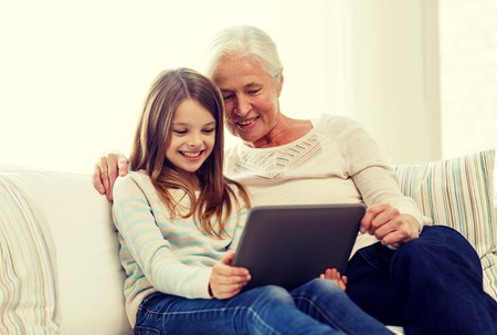 computer generation: family, generation, technology and people concept - smiling granddaughter and grandmother with tablet pc computer sitting on couch at home
