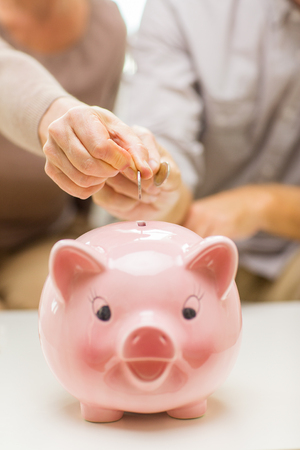 age old: family, savings, age and people concept - close up of senior couple hands putting coin money to piggy bank