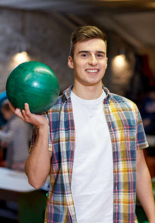 entertainment concept: people, leisure, sport and entertainment concept - happy young man holding ball in bowling club