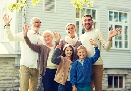 house family: gesture, happiness, generation, home and people concept - happy family waving hands in front of house outdoors