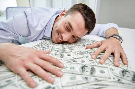 business, people, success and fortune concept - happy businessman with heap of dollar money in office Stock Photo