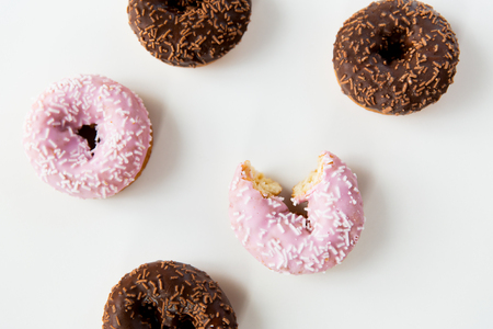 junkfood: food, junk-food and eating concept - close up of glazed donuts over white Stock Photo