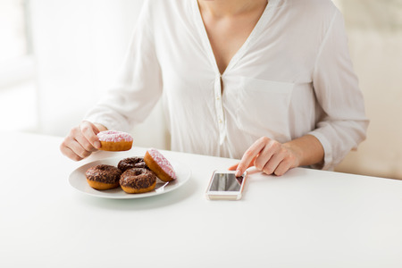 unhealthy diet: people, junk food, diet, technology and unhealthy eating concept - close up of hands with smart phone and donuts counting calories and sitting at table at home