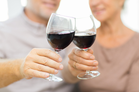 clinking: family, holidays, drinks, age and people concept - close up of happy senior couple clinking glasses with red wine at home