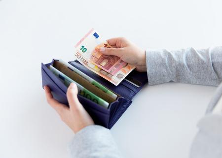 dinero euros: negocios, las finanzas, el ahorro, la banca y la gente concepto - cerca de manos de la mujer con la carpeta y el dinero del euro