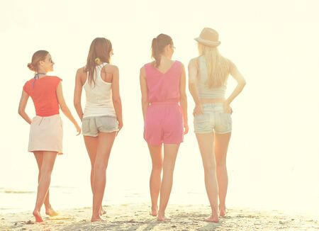 women friendship: summer vacation, holidays, travel, friendship and people concept - group of young women walking on beach