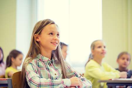 elementary school: education, elementary school, learning and people concept - group of school kids with notebooks sitting in classroom Stock Photo