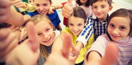aprendizaje: educación, escuela primaria, el aprendizaje, el gesto y el concepto de personas - grupo de niños de la escuela y que muestra los pulgares para arriba en el aula Foto de archivo