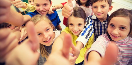 elementary school: education, elementary school, learning, gesture and people concept - group of school kids and showing thumbs up in classroom