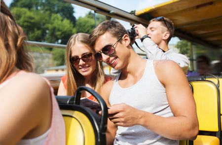 guidebook: friendship, travel, vacation, summer and people concept - smiling couple in sunglasses with guidebook traveling by tour bus