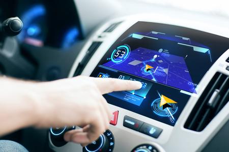 transporte: transporte, destino, tecnologia moderna e as pessoas conceito - mão masculina em busca de rota utilizando sistema de navegação na tela do painel do carro