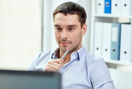 tecnología informatica: negocio, la gente y la tecnología concepto - joven hombre de negocios con el ordenador portátil en la oficina
