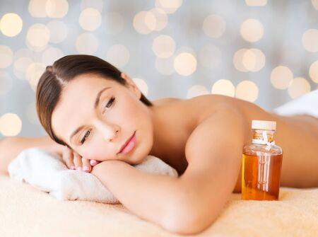 body oil: spa, beauty, people and body care concept - happy woman lying on the massage desk with oil bottle over holidays lights background Stock Photo