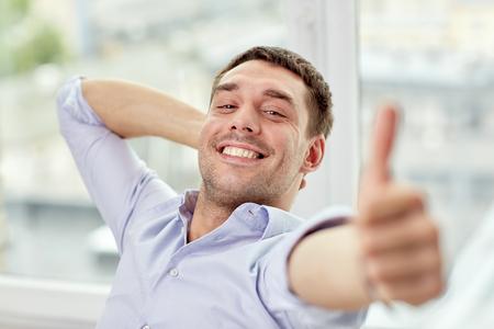 Geschäft, Leute und Gestenkonzept - lächelnder Mann, der sich Daumen zu Hause oder Büro zeigt