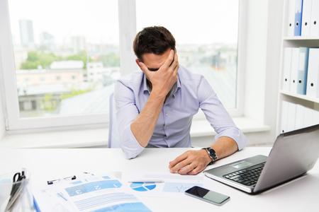 ビジネス、人々、失敗、書類、技術コンセプト - ラップトップ コンピューターとペーパーのオフィスで働くビジネスマン