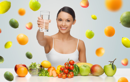 drink water: people, diet and vegetarian concept - happy asian woman with healthy food showing glass of water over gray background with falling fruits Stock Photo
