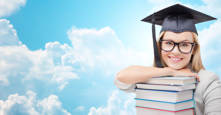 trencher: education, high school, knowledge, and people concept - picture of happy student girl or woman in trencher cap with stack of books over blue sky and clouds background