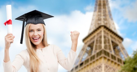 trencher: education, school, knowledge, graduation and people concept - happy student girl or woman in trencher cap with diploma certificate over paris eiffel tower background