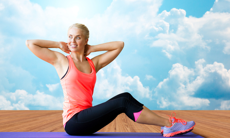 situp: fitness, sport, exercising and people concept - smiling woman doing sit-up on mat over wooden floor and sky with white clouds background Stock Photo