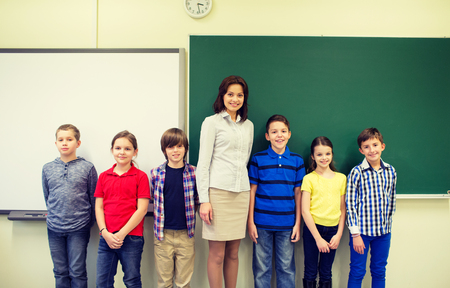 school classroom: education, elementary, gesture and people concept - group of school kids and teacher in classroom Stock Photo