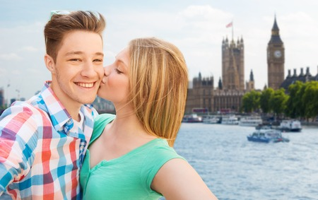 england: travel, vacation, technology and friendship concept - happy couple taking selfie over houses of parliament and thames river in london background