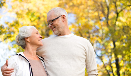 embracing couple: family, age, season and people concept - happy senior couple over autumn trees background Stock Photo