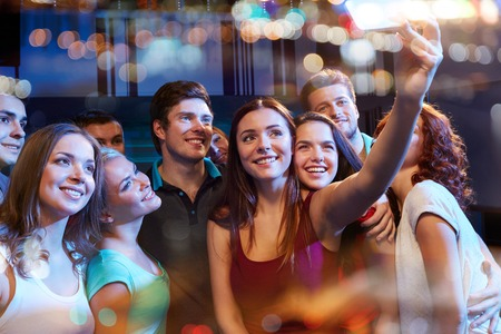 latin people: party, technology, nightlife and people concept - smiling friends with smartphone taking selfie in club
