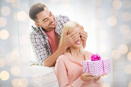 guess: relationships, love, people, birthday and valentines day concept - happy man covering woman eyes and giving gift box at home over holidays lights background Stock Photo