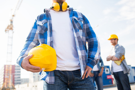 construction site helmet: building, protective gear and people concept - close up of builder holding yellow hardhat or helmet at construction site