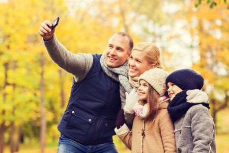 family, childhood, season, technology and people concept - happy family taking selfie with smartphone in autumn park Stock Photo