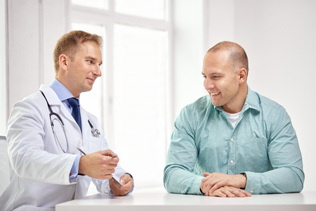 men talking: medicine, health care, people and prostate cancer concept - happy male doctor with clipboard and patient meeting and talking at hospital