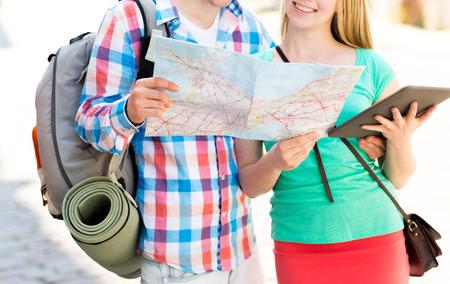 mochila de viaje: los viajes, el turismo, las vacaciones de verano y el concepto de la gente - sonriente pareja con el mapa, ordenador Tablet PC y la mochila en la ciudad Foto de archivo