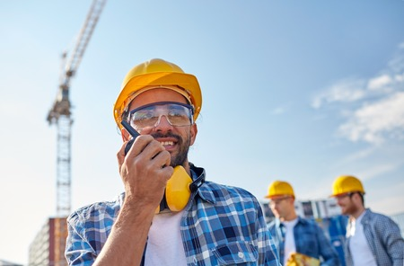 radio communication: industry, building, technology and people concept -male builder in hardhat with walkie talkie or radio at construction site