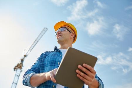 微笑むタブレット pc コンピューターとヘルメットのビルダーの建設現場で建築のグループ - ビジネス、建築、産業、技術、人の概念