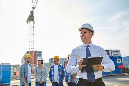 negocio, construcción, trabajo en equipo y las personas concepto - grupo de constructores sonrientes y arquitecto con el sujetapapeles en sombreros duros en el sitio de construcción Foto de archivo