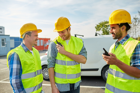 visible: industry, building, technology and people concept - happy male builders in high visible vests with walkie talkie or radio outdoors Stock Photo