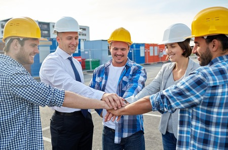 international business agreement: business, building, partnership, gesture and people concept - smiling builders and architects in hardhats with hands on top outdoors