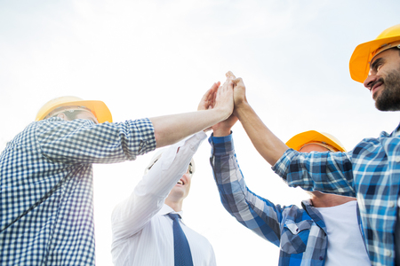 business, building, partnership, gesture and people concept - close up of smiling builders in hardhats making high five outdoors Imagens