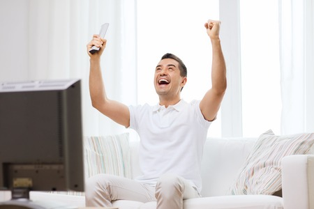 people watching: sports, happiness and people concept - smiling man watching sports on tv and supporting team at home Stock Photo