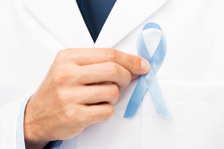 cuidado de la salud, profesión, las personas y concepto de la medicina - primer plano de la mano masculina médico con el cielo cinta de la conciencia del cáncer de próstata Foto de archivo