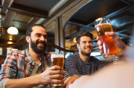 drinks on bar: people, leisure, friendship and and bachelor party concept - happy male friends drinking beer at bar or pub
