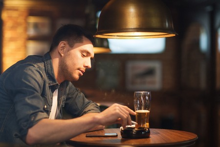 shake off: people and bad habits concept - man drinking beer and smoking and shaking off ashes of cigarette at bar or pub