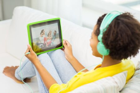 people watching: people, technology and leisure concept - close up of happy african american young woman lying with tablet pc computer and headphones listening to music and watching video at home Stock Photo