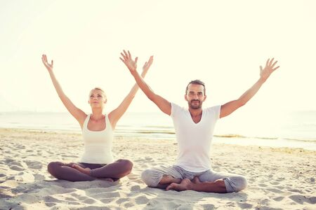 sport fitness: fitness, sport, friendship and lifestyle concept - smiling couple making yoga exercises sitting on sand outdoors