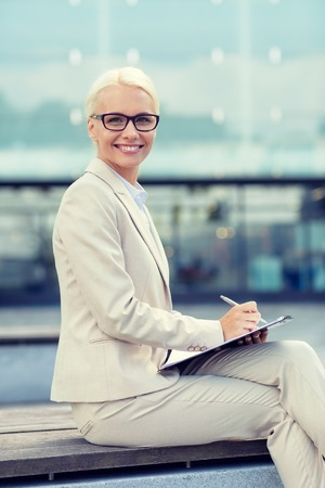woman  glasses: business, people and education concept - young smiling businesswoman in glasses with notepad over office building Stock Photo