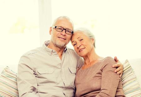 familie, relaties, leeftijd en mensen concept - gelukkig senior paar knuffelen op de bank thuis